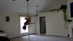 Woman learning how to pole dance at home