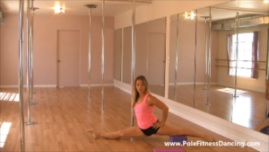 Girl doing a box split stretch to improve pole fitness flexibility