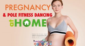 A pregnant lady holding a yoga matt and weights getting ready to pole dance